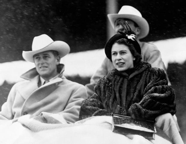 File photo dated 21/10/51 of Queen Elizabeth II and the Duke of Edinburgh covered with blankets watching a 'stampede' rodeo staged especially for them in Calgary, Alberta, during their tour of Canada
