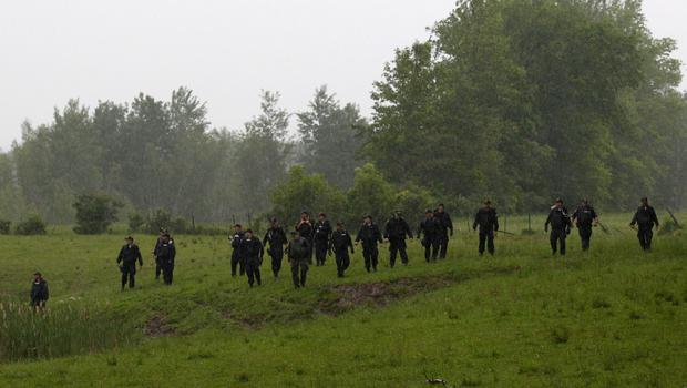 Law enforcement officers search a field near Willsboro, New York June 9, 2015. REUTERS/Chris Wattie