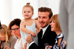 David Beckham holds Harper as he talks to Vogue's Anna Wintour before one of Victoria's shows last year Picture: Reuters
