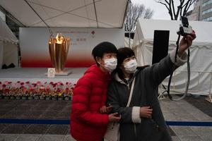 Two spectators take a selfie with the Olympic Flame during a ceremony in Fukushima City, Japan on Tuesday March 24, 2020. (AP Photo/Jae C. Hong)