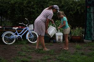 Eight-year-old Chelsea Symonds helps her mother Sally Roser to water plants in their yard with buckets of collected rainwater in the drought-affected town of Murrurundi, New South Wales, Australia February 17, 2020. Picture taken February 17, 2020.  REUTERS/Loren Elliott