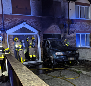 Arson attack: Firefighters at the house after a car was driven into it and set alight