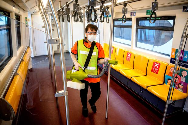 An employee sprays disinfectant in a BTS commuter train carriage as a preventive measure against the spread of COVID-19 in Bangkok. (Photo by Mladen ANTONOV / AFP)
