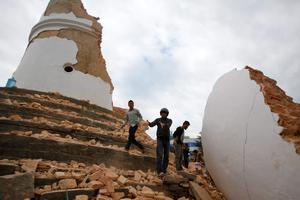 Volunteers work to remove debris at the historic Dharahara tower, a city landmark, after an earthquake in Kathmandu, Nepal, Saturday, April 25, 2015. A strong magnitude-7.9 earthquake shook Nepal's capital and the densely populated Kathmandu Valley before noon Saturday, causing extensive damage with toppled walls and collapsed buildings, officials said. (AP Photo/ Niranjan Shrestha)