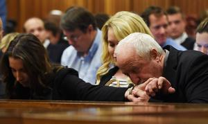 Henke Pistorius (R) kisses the hand of his daughter Aimee Pistorius (L) during the judgement of his son Olympic and Paralympic track star Oscar Pistorius at the North Gauteng High Court in Pretoria, September 11, 2014. A South African judge cleared Oscar Pistorius of all murder charges on Thursday, saying prosecutors had failed to prove the Olympic and Paralympic track star intended to kill his girlfriend or an imagined intruder on Valentine's Day last year. REUTERS/Phill Magakoe.