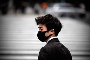 A man wearing a face mask waits to walk over Shibuya crossing in Tokyo, Japan. (Photo by Carl Court/Getty Images)