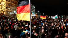 Participants hold German national flags during a demonstration called by anti-immigration group PEGIDA