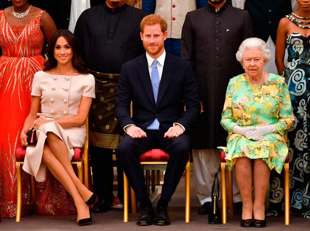 Queen Elizabeth II with the Duke and Duchess of Sussex during a group photo at the Queen's Young Leaders Awards Ceremony at Buckingham Palace, London
