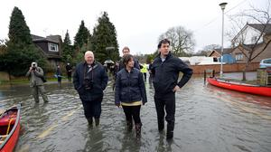 Labour leader Ed Miliband (right) and Victoria Groulef (centre), Labour's Parliamentary Candidate for Reading West, during a visit to the view recent flooding in Purley on Thames in Berkshire.