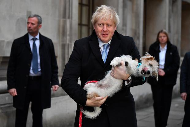 Dog day afternoon: Britain's Prime Minister Boris Johnson holds his dog Dilyn as he leaves a polling station at the Methodist Central Hall in London yesterday. Photo: Reuters