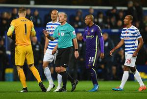 Referee Mike Dean talks to Joe Hart as Charlie Austin's goal is disallowed. Photo credit: Tom Dulat/Getty Images