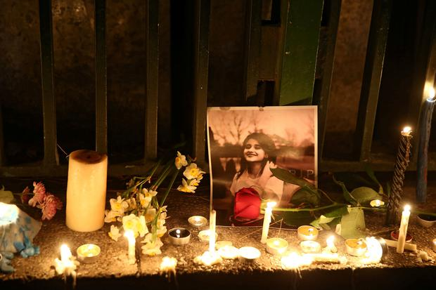 A picture is seen next to candles lit by people and families of the victims of the crash of the Boeing 737-800 plane, flight PS 752, in Tehran, Iran January 11, 2020. Nazanin Tabatabaee/WANA (West Asia News Agency)