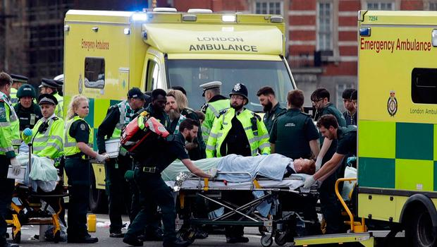 Emergency services transporting an injured person to an ambulance, close to the Houses of Parliament in London. Photo: AP