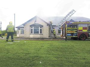 Response: Firefighters deal with the aftermath of the lightning strike at Kevin and Breda Clifford's home. Photo: Press 22