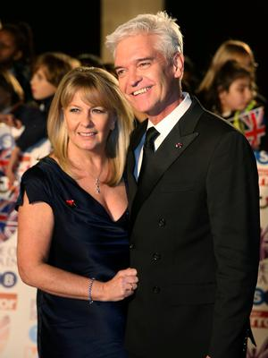 SUPPORT: TV presenter Phillip Schofield with his wife Stephanie Lowe. Picture: Reuters
