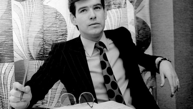 Portrait of Irish actor Pierce Brosnan sitting behind an office desk dressed in a suit and tie, London, United Kingdom, circa 1978. (Photo by Jeremy Fletcher/Redferns)