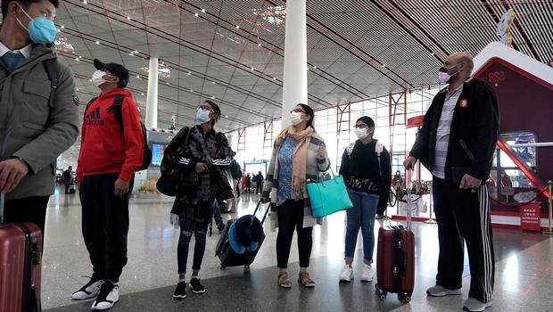 Foreign travellers wearing masks check their flight's departure information at Beijing International Airport. Photo: Reuters