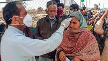 Security: A Pakistani health official checks the temperature of a pilgrim returning home from Iran. Photo: STR/AFP via Getty Images