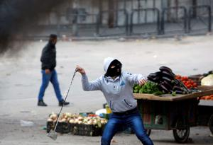A Palestinian uses a sling to hurl stone at Israeli soldiers during clashes in the West Bank city of Hebron. Reuters/ Mussa Qawasma