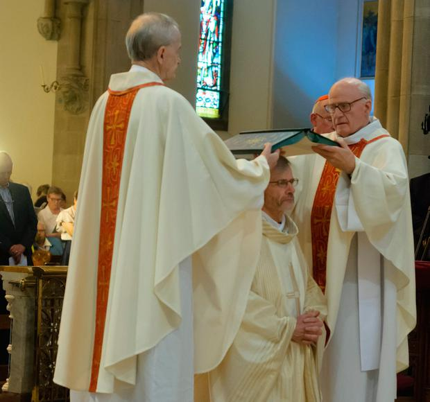 The two brothers hold the Book of the Gospels over the head of the new bishop. Photo: Liam McArdle