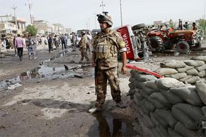 Iraqi security force members inspect the site of a car bomb attack in Basra