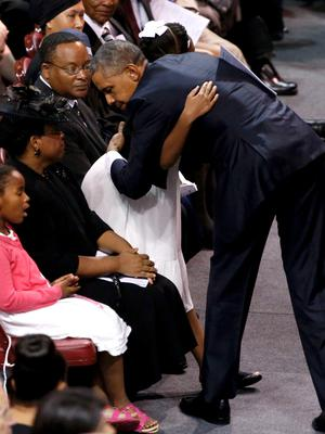 U.S. President Barack Obama hugs Eliana Pinckney as he visits with her mother Jennifer and sister Malana aftercompleting his eulogy for her father Rev. Clementa Pinckney during funeral services for Pinckney in Charleston, South Carolina June 26, 2015. Pinckney is one of nine victims of a mass shooting at the Emanuel African Methodist Episcopal Church. REUTERS/Jonathan Ernst