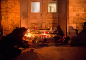 A man places candles in front of the home of singer and poet Leonard Cohen  (Paul Chiasson/The Canadian Press via AP)