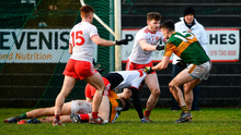 Seeing red: Tyrone's Ben McDonnell and Kerry's David Clifford tussle on the ground during yesterday's encounter at Edendork GAC, Dungannon. Photo by David Fitzgerald/Sportsfile