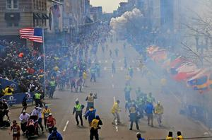People react as an explosion goes off near the finish line of the 2013 Boston Marathon
