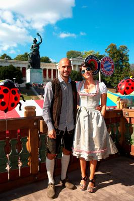 Bayern's coach Pep Guardiola, left, and his wife Cristina Guardiola, right, pose for a photograph as the players of FC Bayern Munich visit the Oktoberfest beer festival 2015 at Theresienwiese in Munich, southern Germany, Wednesday, Sept. 30, 2015. (Alexander Hassenstein/pool via AP)
