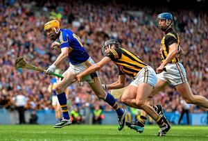Kilkenny's Eoin Larkin is tripped by Tipperary's Paddy Stapleton, which resulted in a penalty for the Cats in the All-Ireland hurling final at Croke Park. Photo: Ramsey Cardy / SPORTSFILE