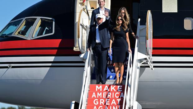 Donald Trump and his wife Melania (front right) and son Eric Trump and his wife Lara Yunaska arrive for a rally at Wilmington International Airport in Wilmington, North Carolina on November 5, 2016. / AFP / MANDEL NGAN        (Photo credit should read MANDEL NGAN/AFP/Getty Images)