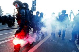 A policeman holds a flare during a protest of members of 'Blockupy' anti-capitalist movement near the European Central Bank (ECB) building before the official opening of its new headquarters in Frankfurt