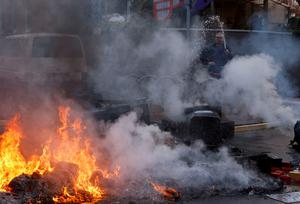 A resident extinguishes a burning barricade during a protest of members of 'Blockupy' anti-capitalist movement near the European Central Bank (ECB) building before the official opening of its new headquarters in Frankfurt