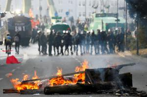 A barricade burns in front of policemen during a protest of members of 'Blockupy' anti-capitalist movement near the European Central Bank (ECB) building before the official opening of its new headquarters in Frankfurt