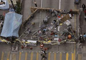 People walk past a barricade set up by pro-democracy protesters in the occupied area of the Mong Kok district in Hong Kong Monday, Nov. 24, 2014. (AP Photo/Vincent Yu)