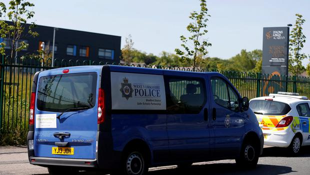 Police vehicles outside Dixons Kings Academy in Bradford. A 14-year-old boy is being hunted by police after a teacher was stabbed at the school. PRESS ASSOCIATION Photo. Picture date: Thursday June 11, 2015. The 50-year-old male teacher was taken to hospital for treatment to a stab wound to his body. See PA story POLICE School. Photo credit should read: Lynne Cameron/PA Wire