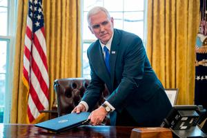 Vice President Mike Pence picks a folder after President Donald Trump departed the Oval Office of the White House, in Washington. (AP Photo/Andrew Harnik)