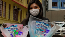 Flower shop owner Iris Leung wears her protective face mask as she delivers flowers with masks to customers on Valentine's Day in Hong Kong, on Friday. Photo: AP