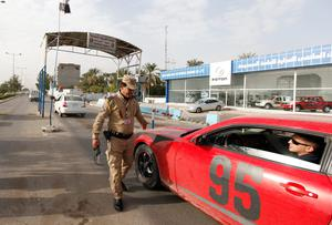 Iraqi security personnel inspect a car using a scanning device at a checkpoint in Baghdad