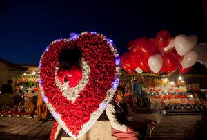 A man sits on a roadside next to a paper-flower decoration as he holds heart-shaped balloons, waiting for costumers on the ahead of Valentine's Day in Islamabad February 13, 2014.   REUTERS/Mian Khursheed  (PAKISTAN - Tags: SOCIETY)