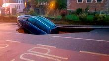 Picture tweeted by the Metropolitan Police showing a car which has partially disappeared down a sinkhole in Woodland Terrace in Greenwich, south-east London. Credit: Metropolitan Police/PA Wire