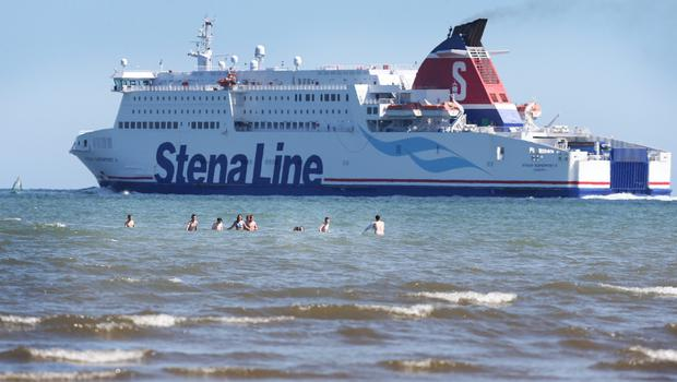 Young teenagers on Dollymount beach as the Stena Line sets sail during the warm weather. Pic Steve Humphreys