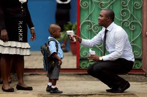 A school official takes a young  pupil's temperature using an infrared digital laser thermometer in front of the premises as private schools resume services in Lagos, Nigeria yesterday. Reuters