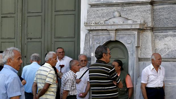 People, most of them pensioners, line up outside a closed National Bank branch at the bank's headquarters in Athens, Greece closed its banks and imposed capital controls on Sunday to check the growing strains on its crippled financial system, bringing the prospect of being forced out of the euro into plain sight.  REUTERS/Alkis Konstantinidis
