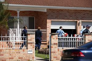 Police investigators work at a home at Guildford in suburban Sydney, Australia after about 800 federal and state police officers raided more than two dozen properties as part of an operation  AP Photo/Rick Rycroft