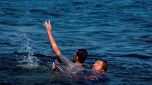 Local resident Dimitris Karapanagiotis, right,  rescues an Afghan migrant whose boat stalled at sea while crossing with others from Turkey to the island of Lesbos, Greece, on Saturday, Sept. 19, 2015.  (AP Photo/Petros Giannakouris)