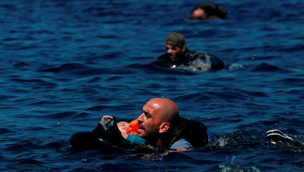 A Syrian refugee holding a baby in a lifetube swims towards the shore after their dinghy deflated some 100m away before reaching the Greek island of Lesbos, September 13, 2015. Of the record total of 432,761 refugees and migrants making the perilous journey across the Mediterranean to Europe so far this year, an estimated 309,000 people had arrived by sea in Greece, the International Organization for Migration (IMO) said on Friday. About half of those crossing the Mediterranean are Syrians fleeing civil war, according to the United Nations refugee agency. REUTERS/Alkis Konstantinidis      TPX IMAGES OF THE DAY