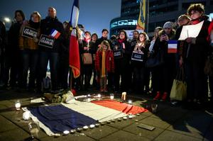 People gather for a vigil Wednesday, Jan. 7, 2014 in Seattle after a shooting at the French satirical publication Charlie Hebdo left 12 people dead. (AP Photo/seattlepi.com, Joshua Trujillo)