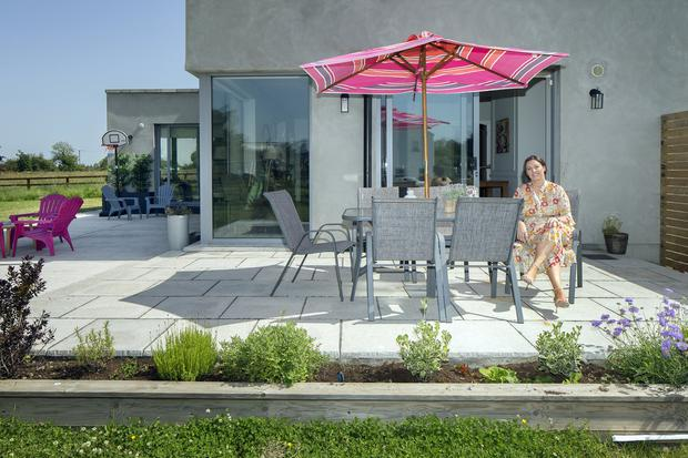 Ciara on her sun patio; there are doors to it from the kitchen and from the children's playroom, which is off the kitchen. Ciara believes it's essential to have the kids as close to the kitchen as possible. Photo: Tony Gavin